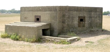 A Pillbox (millitary definition) from WW2 in Cudmore Grove. A concrete low-roof structure with a square rifle whole. in Soldiers would hide/position in these structures and fire through the rifle hole at an invading enemy. The Pillbox served as a defense/fortress